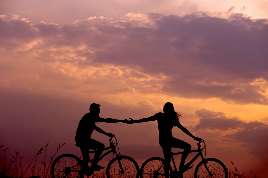 A man and a woman cycling in the evening