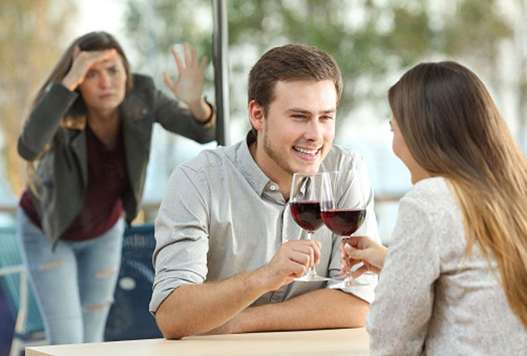 A woman watching the couple which is in the restaurant drinking red wine