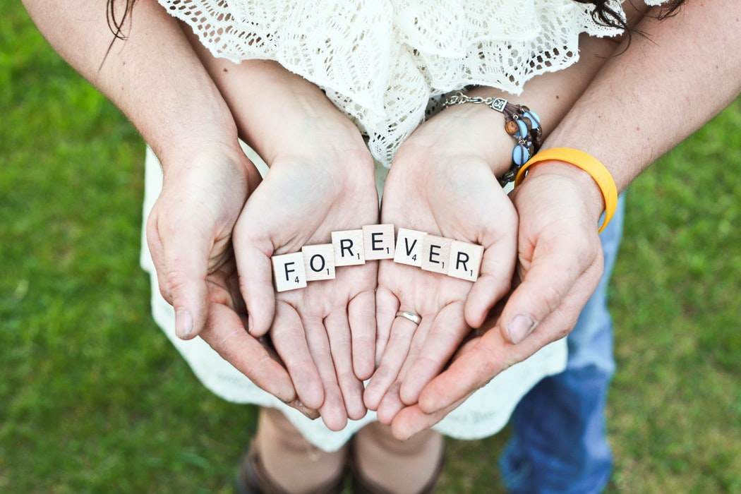Forever word in the hands of the couple