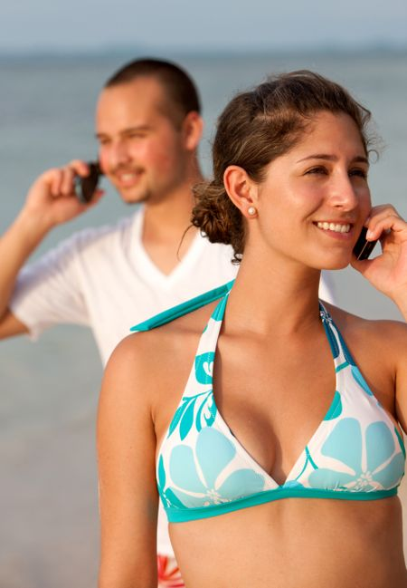 A girl and a man talking ove rthe phones at the seaside