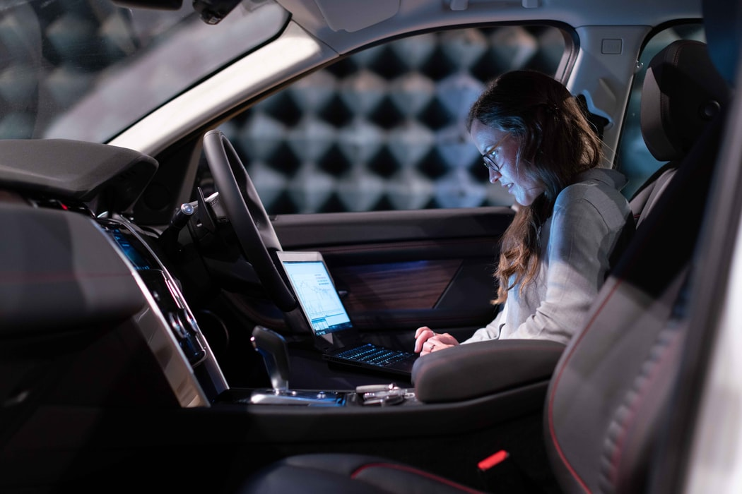 A lady in the car using computer